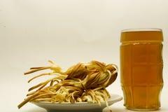 Trenza del queso con la cerveza en un fondo ligero imagenes de archivo