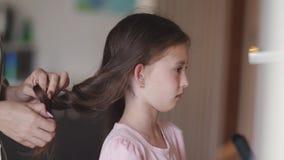 Trenzas de la mamá y peinar a una pequeña hija trastornada almacen de video