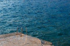 Treppe auf dem Strand Tauchen im blauen Meerwasser Stockfotografie