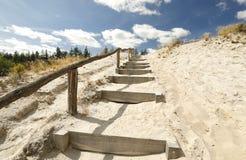 Treppe auf Sand zum blauen Himmel mit Wolken lizenzfreie stockfotografie