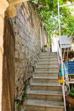 Treppe entlang der Steinwand in altem Budva, Montenegro Lizenzfreies Stockfoto