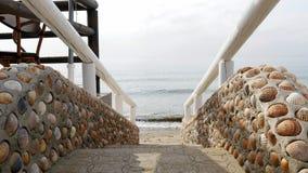 Treppe hergestellt von den Oberteilen und von hölzernem Handlauf, die zu das Meer führen Stockfotos