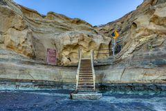 Treppe stellt einen Weg zur Verfügung, damit Wanderer vom Strand herauf die braunen Klippen aufsteigen stockbild