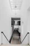 Treppe und ein Korridor mit weißen Wänden im modernen Gebäude Stockbild