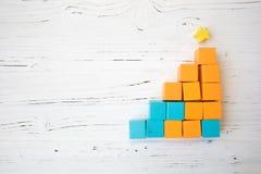 Treppe von den hölzernen Würfeln des orange und blauen Spielzeugs auf weißem hölzernem Hintergrund Stockbild