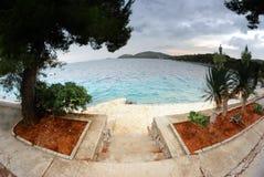 Treppe zum Strand, zum klaren Wasser und zum bewölkten Himmel in Kroatien Dalmatien Lizenzfreie Stockfotografie