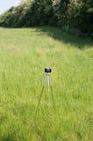 Treppiede di macchina fotografica d'annata sul prato verde Fotografia Stock