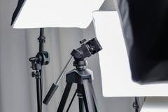 Treppiede di macchina fotografica in uno studio della foto con l'attrezzatura del fulmine Fotografia Stock Libera da Diritti