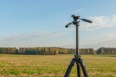 Treppiede per la macchina fotografica nel campo contro un cielo blu, nel campo ed in foresta Fotografie Stock Libere da Diritti