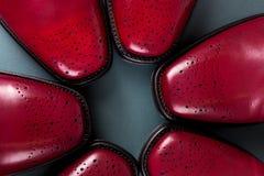 Tres abarcas de los pares en un círculo Zapatos rojos de Oxford en fondo azul Visión superior Fotografía de archivo