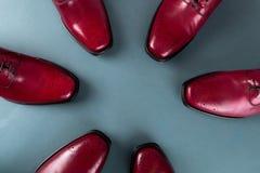 Tres abarcas de los pares en un círculo Zapatos rojos de Oxford en fondo azul Visión superior Fotos de archivo libres de regalías