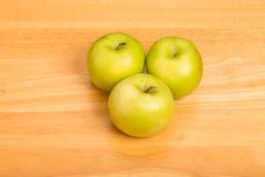 Tres abuelita Smith Apples en el contador de madera Imagenes de archivo