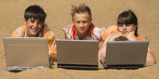 Tres adolescencias con las computadoras portátiles Foto de archivo