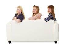 Tres adolescencias de las muchachas que se sientan en el sofá Foto de archivo libre de regalías