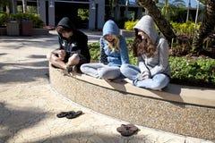 Tres adolescencias que se sientan junto Imagen de archivo libre de regalías