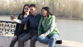 Tres adolescentes asiáticos hermosos que toman un selfie divertido con su smartphone metrajes