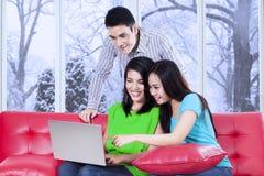 Tres adolescentes con el ordenador portátil en casa Foto de archivo libre de regalías