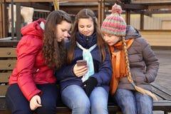 Tres adolescentes con el teléfono móvil Fotos de archivo