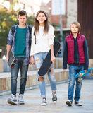 Tres adolescentes con los monopatines al aire libre Fotos de archivo