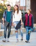 Tres adolescentes con los monopatines al aire libre Imagen de archivo libre de regalías