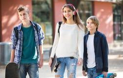 Tres adolescentes con los monopatines al aire libre Imagenes de archivo