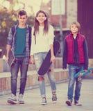 Tres adolescentes con los monopatines al aire libre Fotos de archivo libres de regalías