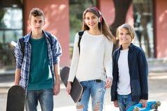 Tres adolescentes con los monopatines al aire libre Imágenes de archivo libres de regalías