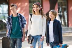 Tres adolescentes con los monopatines al aire libre Foto de archivo