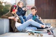Tres adolescentes con los teléfonos al aire libre Fotografía de archivo
