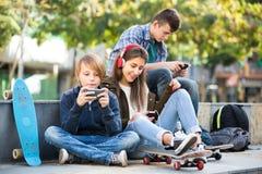 Tres adolescentes con los teléfonos al aire libre Imagen de archivo libre de regalías