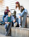 Tres adolescentes con los teléfonos al aire libre Imagenes de archivo