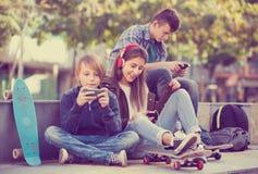 Tres adolescentes con los teléfonos al aire libre Foto de archivo