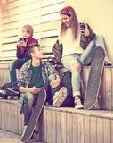 Tres adolescentes con los teléfonos al aire libre Foto de archivo libre de regalías