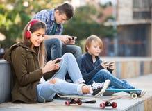 Tres adolescentes con los teléfonos al aire libre Fotos de archivo libres de regalías