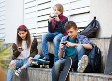 Tres adolescentes con smartphones Foto de archivo libre de regalías