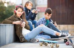 Tres adolescentes con smartphones Imagenes de archivo
