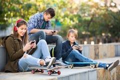 Tres adolescentes con smartphones Fotografía de archivo libre de regalías