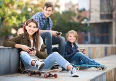 Tres adolescentes con smartphones adentro al aire libre Imagenes de archivo