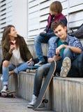 Tres adolescentes con smartphones adentro al aire libre Fotografía de archivo
