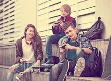 Tres adolescentes con smartphones adentro al aire libre Foto de archivo