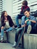 Tres adolescentes con smartphones adentro al aire libre Imagen de archivo libre de regalías