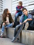 Tres adolescentes con smartphones adentro al aire libre Imágenes de archivo libres de regalías