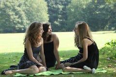 Tres adolescentes disfrutan de un día en el parque Imagen de archivo