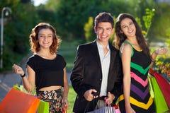 Tres adolescentes elegantes hacia fuera que hacen compras junto Imagen de archivo libre de regalías