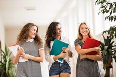 Tres adolescentes en pasillo de la High School secundaria durante rotura Imagen de archivo