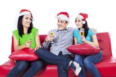 Tres adolescentes en vino de consumición del sombrero de santa Imagen de archivo libre de regalías