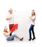 Tres adolescentes felices en sombreros de la Navidad que señalan en una bandera Foto de archivo libre de regalías