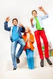 Tres adolescentes felices que saltan en el sofá blanco Imágenes de archivo libres de regalías