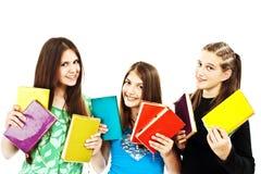 Tres adolescentes jovenes con los libros coloreados Imagenes de archivo