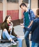 Tres adolescentes que cuelgan hacia fuera al aire libre Imagenes de archivo